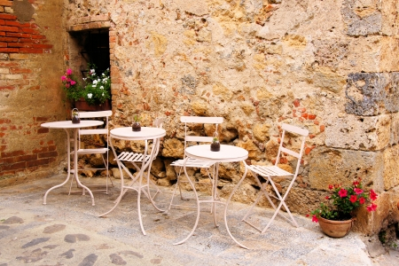 Cafe tables and chairs outside in a quaint corner of Tuscany, Italy photo