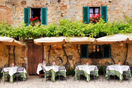 Cafe tables and chairs outside a quaint stone building in Tuscany, Italy Stock Photo