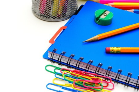 Notebook with school supplies, close up over white  photo