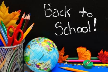 teaching crayons: Back to School written on a blackboard with school supplies