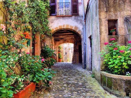 Overspannen geplaveide straat in een Toscaans dorp, Italië