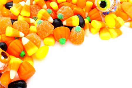 Halloween corner border of varied candies over white photo