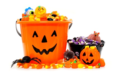 Halloween Jack o Lantern candy bowls with assorted candy over white photo