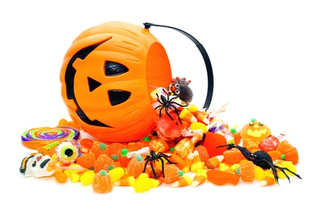 Halloween candy spilling from a Jack o Lantern holder Imagens