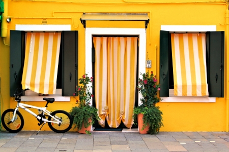 Vibrant yellow house front in Burano, Venice, Italy