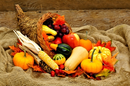 Harvest or Thanksgiving cornucopia filled with vegetables on a burlap and wood background photo