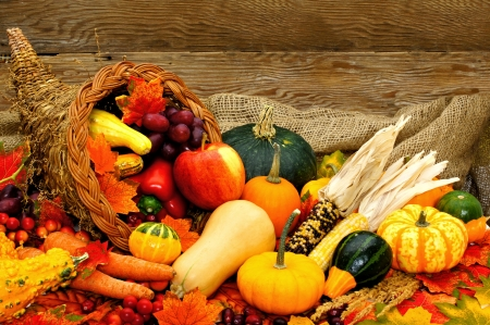 Harvest or Thanksgiving cornucopia filled with vegetables against wood