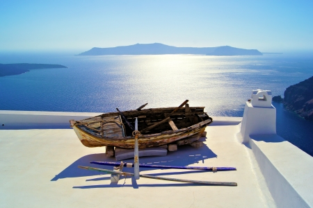 firostefani: Old wooden boat resting on the white rooftops of Santorini, Greece