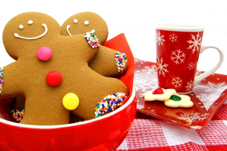 Gingerbread Men in a bowl with cookies and festive mug in background photo