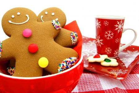 fondo chocolate: Los hombres de pan de jengibre en un taz�n con galletas y taza festiva en el fondo Foto de archivo