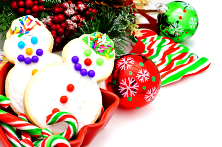Christmas collection of cookies, candy, baubles and branches over white photo