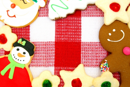 Border of Christmas cookies over a red and white checked cloth photo