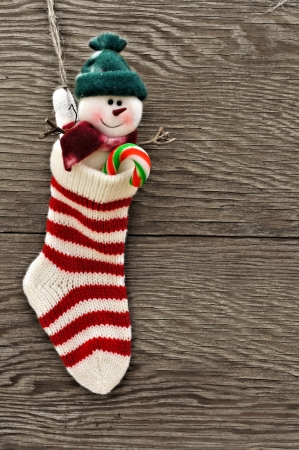 Christmas stocking with snowman against a wooden  photo