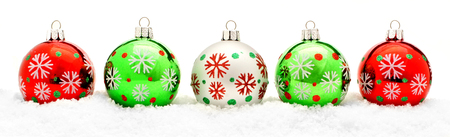 Border of colorful Christmas baubles in fresh snow photo