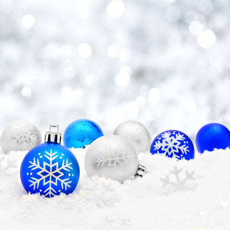 Blue and silver Christmas baubles in snow with silver light background
