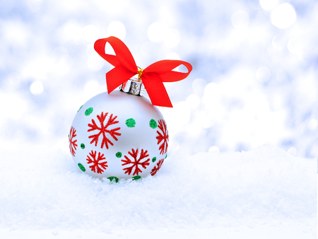 Single Christmas bauble in snow with silver light background photo
