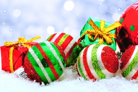 Christmas baubles and gifts in snow with silver light background photo
