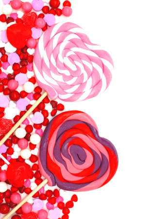 shaped: Heart shaped lollipops and candy border over white Stock Photo