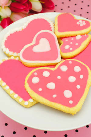 Plate of heart shaped cookies with pink frosting and pink pattered