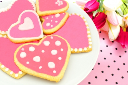 Plate of heart shaped cookies with pink frosting, flowers and pink pattered