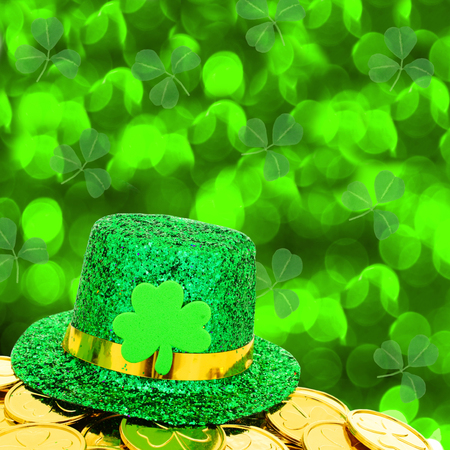 saint paddy's: St Patricks Day hat and gold coins with green shamrock background Stock Photo
