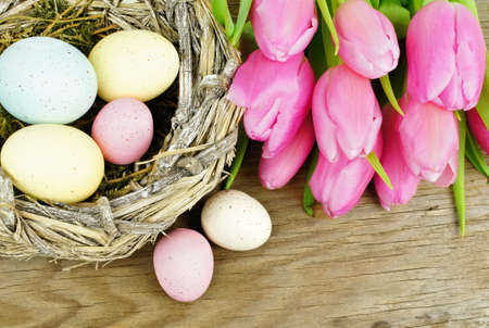 Easter nest with eggs and pink tulip flowers on wooden  photo