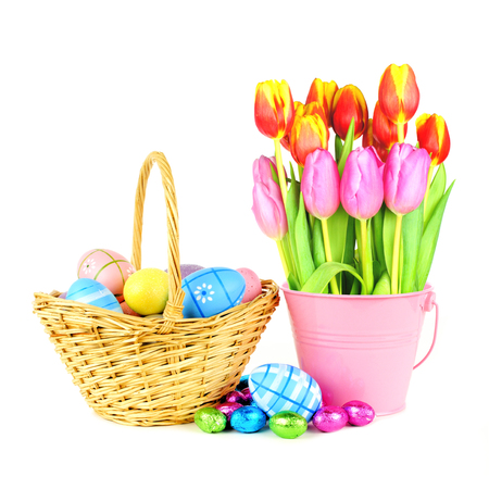 Easter basket with eggs and a bunch of tulips over a white background photo