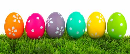 decoratif: Ligne des oeufs de Pâques sur l'herbe avec un fond blanc
