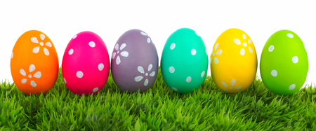 egg hunt: Row of Easter eggs on grass with a white background Stock Photo