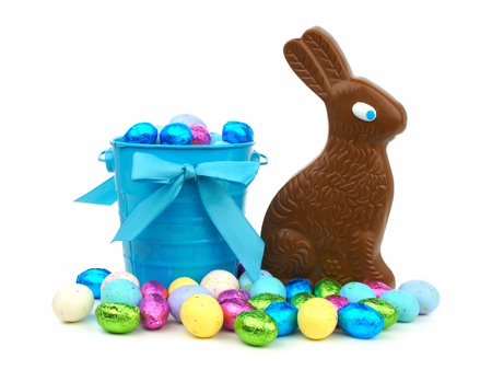 Easter candy in a blue pail with a chocolate bunny over a white background