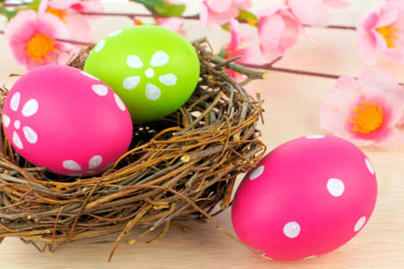 Easter eggs and springtime nest with pink flowers in background  photo