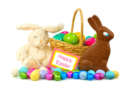 easter message: Happy Easter card with Easter basket, candies and toy bunny over white
