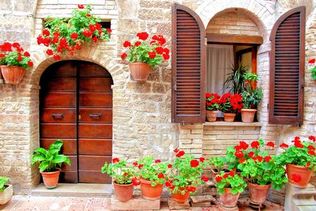 色とりどりの鉢植えの花を持つイタリアの家の前部 写真素材