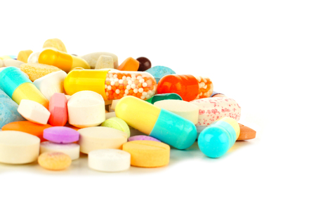 Close up of a pile of assorted medicines over a white background