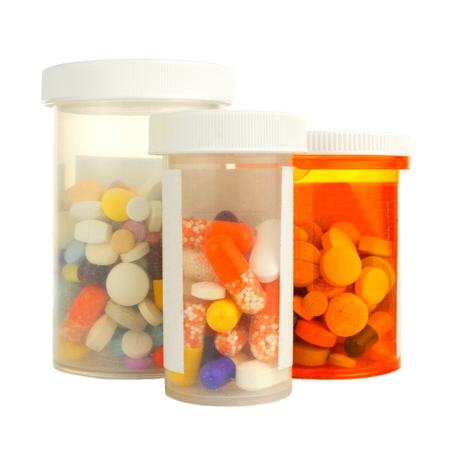Group of three medicine bottles filled with various pills photo