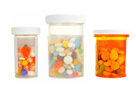 Three pill bottles filled with assorted medications isolated on white photo