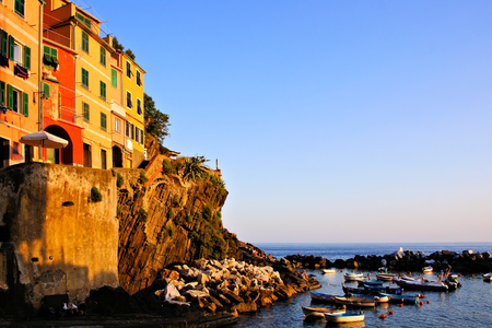 Colorful houses and boats off a coastal village in Italy at sunset photo