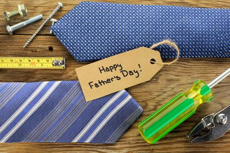 Gelukkig Fathers Day tag met banden en gereedschappen op een houten