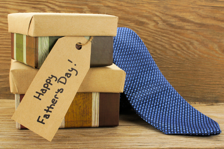 Fathers Day gifts with tag and tie over a wooden background