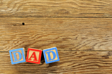 Toy blocks spelling DAD on a wooden background