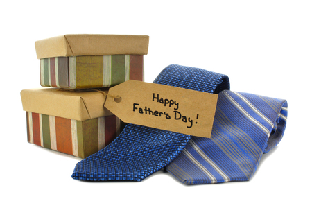 Happy Fathers Day tag with gift boxes and ties over white photo
