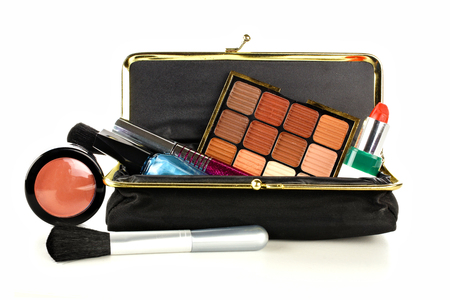 Makeup bag with assorted cosmetics over a white background Stock Photo