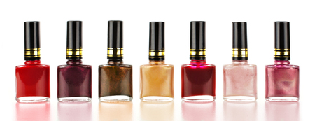nail polish bottle: Row of varied red tone nail polish bottles over a white background