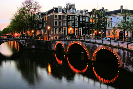 Famous canals of Amsterdam lit up at dusk, Netherlands photo