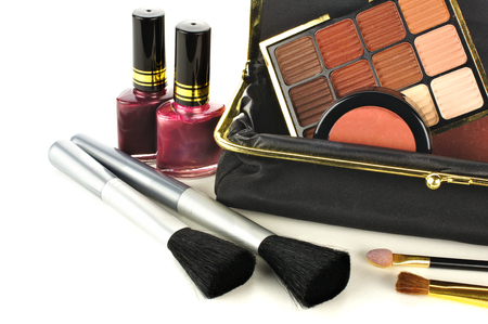 Makeup bag close up with assorted cosmetics over a white background photo