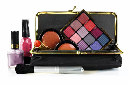 Makeup bag with assorted cosmetics over a white background photo