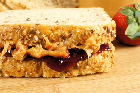 Peanut butter and jelly sandwich close up on wooden background photo