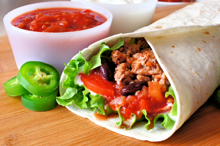 Close up of a burrito filled with meat and vegetables photo