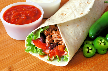 burrito: Burrito filled with meat and vegetables with salsa and peppers on wood Stock Photo