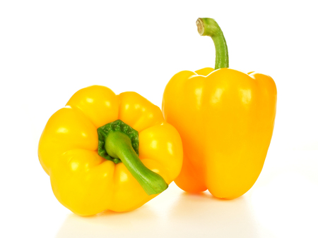 Two yellow peppers over a white background